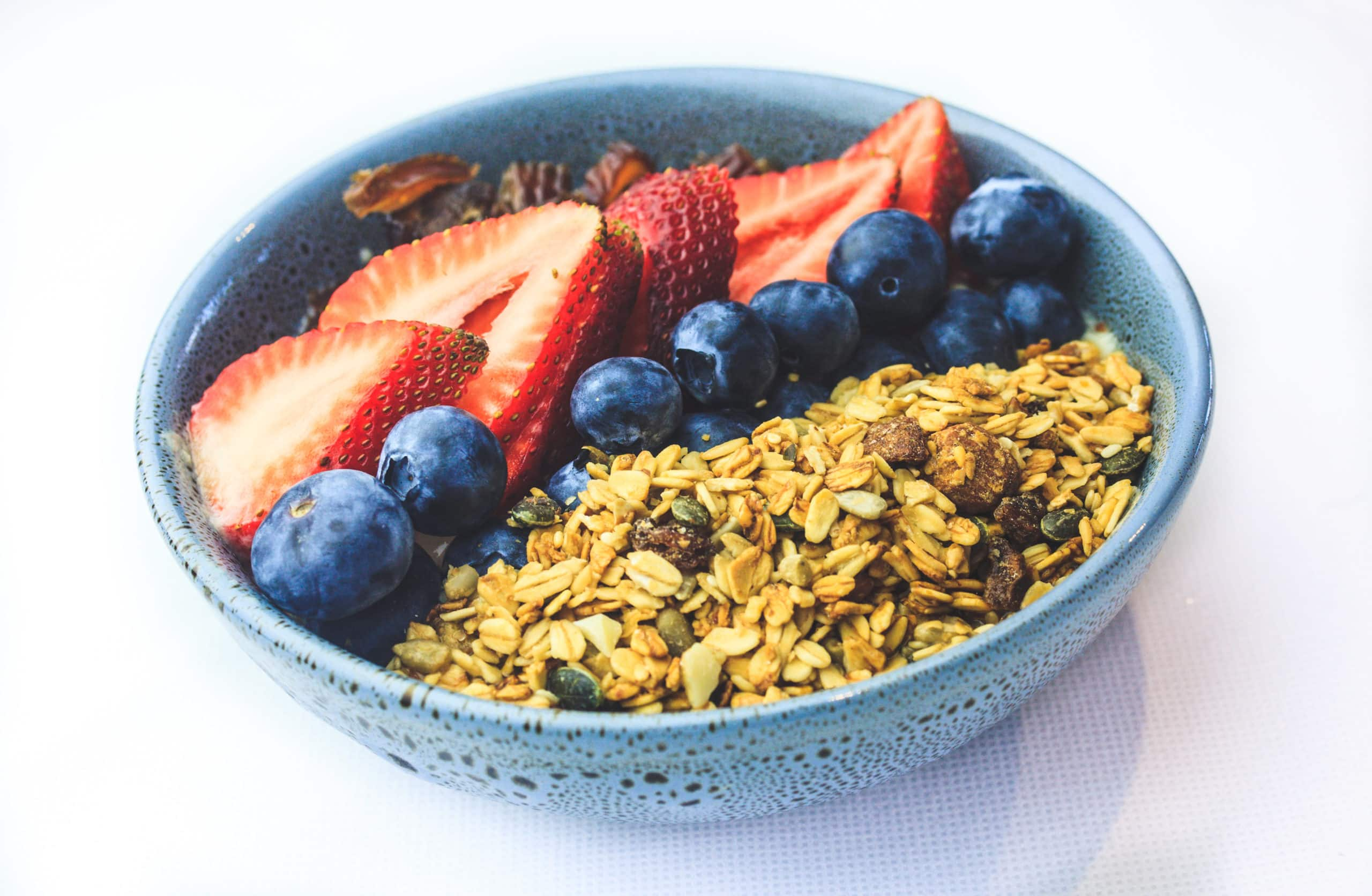 a blue bowl filled with oatmeal and fresh fruit